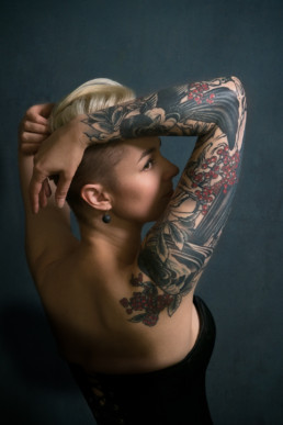 A woman with a blackbird tattoo leans backwards and looks away from the camera. Photograph by Siorna Ashby, a portrait photographer in north London, Finsbury Park.