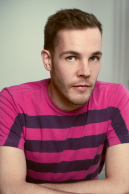 A man in a pink and purple t shirt on a green background. An image of Alex Corbett-Ashby by Siorna Ashby, a portrait photographer in north London, Finsbury Park.