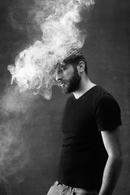 a black and white image of a man vaping with a flat cap and black t shirt from a portrait session in north London. Photograph by Siorna Ashby