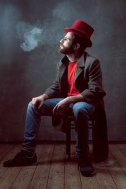 A man vaping in a red top hat sitting on a stool from a portrait session in north London. Photograph by Siorna Ashby