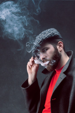 a man vaping with a flat cap and red t shirt from a portrait session in north London. Photograph by Siorna Ashby
