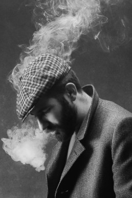 A black and white image of a man vaping with a flat cap looking down from a portrait session in north London. Photograph by Siorna Ashby