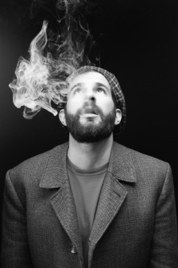 a black and white image of a man vaping with a flat cap from a portrait session in north London. Photograph by Siorna Ashby