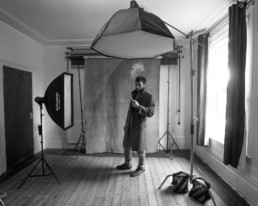 A behind the scenes image in black and white of a man vaping at a portrait session in north London