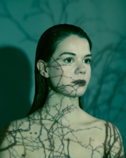 A female creative portrait photoshoot with trees on the face