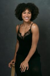 A woman in a black dress smiling at a A London studio photography photoshoot