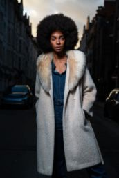A woman in a faux fur white coat at sunset on a London studio photography photoshoot