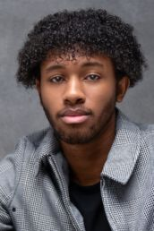 A young man with curly hair and a check jacket at a London photography studio photoshoot