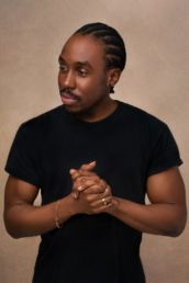 A London studio photoshoot of a man clasping his hands with a gold chain.