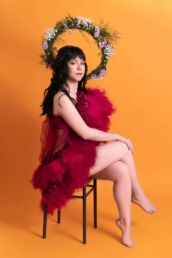 A female London studio photoshoot with flowers and tulle on an orange background
