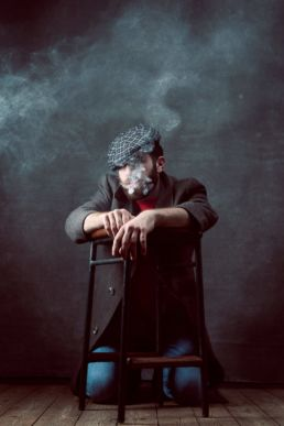 A male London studio photoshoot of a man smoking with a flat cap