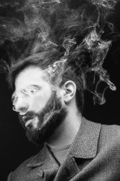 A male London studio photograph of a man with smoke in his face