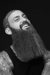 A London studio photograph of a bearded man laughing with tattoos
