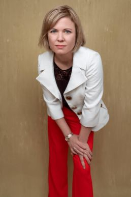 A blonde woman wearing orange trousers leaning into the camera at a London studio photoshoot