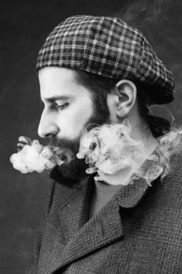A bearded man smoking at a photography studio in London