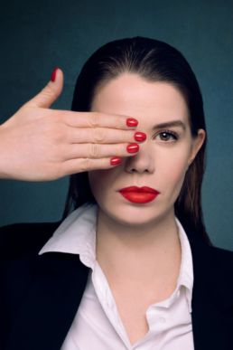 A woman with red lipstick and red nails at a London studio photography session