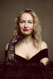 A woman with red lipstick and black lace gloves against a gold backdrop at a London studio photography photoshoot