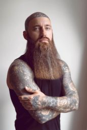 A bearded man with tattoos at a photography studio in London