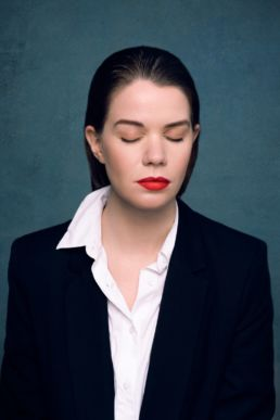 A woman with red lipstick and red nails and eyes closed at a London studio photography session