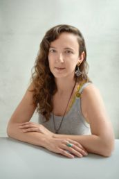 A london headshot photo of a woman's photoshoot with curly hair an earring and a yellow and grey top with pierced lip