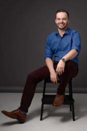 A relaxed mans London headshot photo in a blue shirt and brown shoes