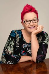 A woman's London headshot photoshoot with glasses and red hair leaning on a table