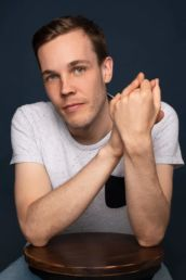A relaxed mens London headshot photo with a white t-shirt and blue background