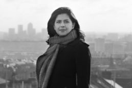 A black and white London headshot photo of a woman's photoshoot with the city of London in the background