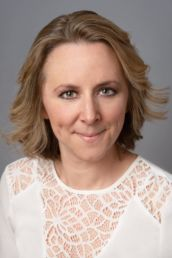 A womand London headshot photography with green eyes and a white top