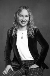 A black and white woman's professional headshot in a velvet jacket and check trousers