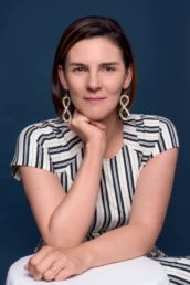 A woman's headshot photograph in London with a stripped dress and big earrings