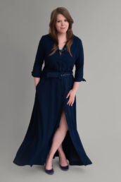 A London portrait photographer wearing a blue dress with crossed legs