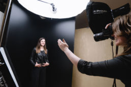 A behind the scenes photoshoot of a London portrait photographer smiling and directing a woman in a leather jacket