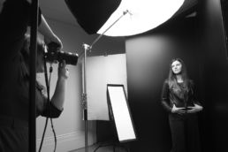 A black and white behind the scenes photoshoot of a London portrait photographer with studio lights and woman posing