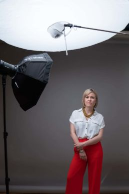 A behind the scenes London photoshoot of a woman in orange trousers and studio lights